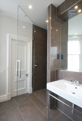 A modern luxury bathroom with SSI True Frameless 12mm glass shower door to ceiling with hydraulic, self closing hinges.