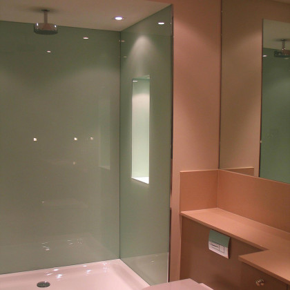 A modern luxury bathroom in London with colour coated glass glass wall cladding. Installed by SSI True Frameless.