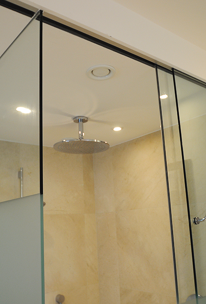 Recess ceiling, sliding shower door and WC enclosure featuring a frosted modesty band on the glass. Installed by SSI True Frameless.