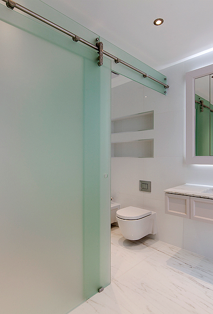 A wet room, luxury marble bathroom in London with an SSI bespoke sliding shower enclosure, frosted Glass.
