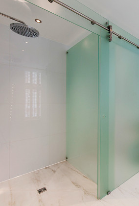 A wet room, luxury marble bathroom in London with an SSI bespoke sliding shower enclosure, frosted Glass. Frameless glass to floor.
