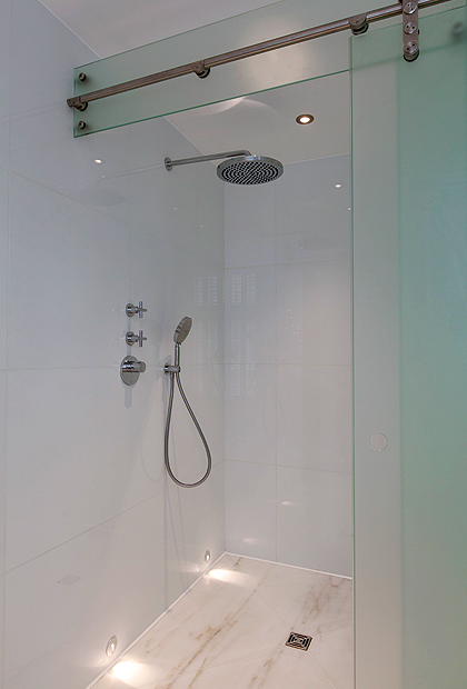 A wet room, luxury marble bathroom in London with an SSI bespoke sliding shower enclosure, frameless glass.