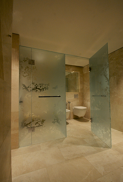 An exclusive luxury bathroom with WC and shower combination enclosure and acid etched tree of life pattern. Installed by SSI True Frameless.