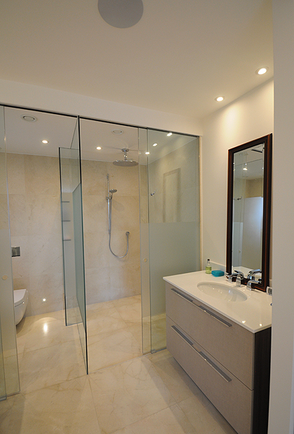 A recess ceiling sliding shower door and WC enclosure featuring a frosted modesty band on the glass. Installed by SSI True Frameless.