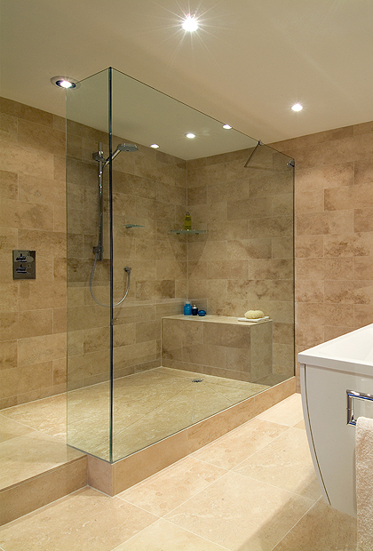 SSI Frameless L Shaped UV bonded Walk-In shower screen installed on stone shower tray