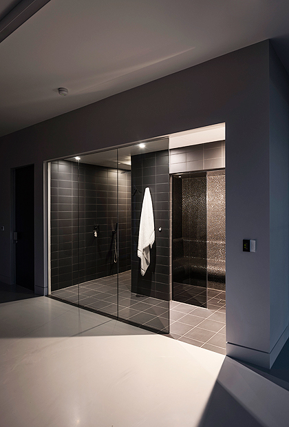 A contemporary luxury bathroom SSI True Frameless, made-to-measure walk in shower panels in Grey, smoked glass.