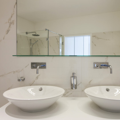 SSI bespoke mirror with invisible wall brackets and UV bonded glass shelf, installed in a luxury bathroom in London.