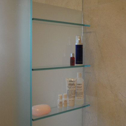 SSI frameless WC and shower combination enclosure with UV bonded glass shelves, installed in a luxury bathroom in London.
