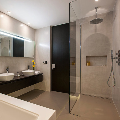 A Luxury bathroom with polished plaster walls, SSI Frameless L Shaped UV bonded Walk-In shower screen