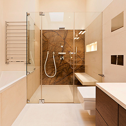 Wet room bathroom with an SSI Frameless shower enclosure at side of bath, installed in a house in London