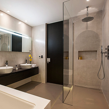 A Luxury bathroom in London with polished plaster walls, SSI Frameless L Shaped UV bonded Walk-In shower screen