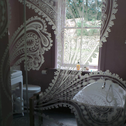 A clear glass shower door with acid etched paisley pattern. Installed by SSI True Frameless.