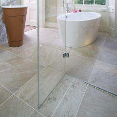 SSI frameless shower enclosure showing seamless glass finish on a linear wet deck tiled shower base. Installed in a luxury bathroom in London.