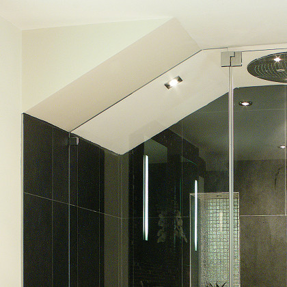 SSI frameless enclosure to ceiling, close up of roof pitch cut in glass, luxury wet room loft bathroom in London