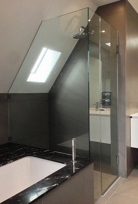 SSI UV bonded bespoke shower enclosure at side of bath with dwarf return and also with roof pitch cut.