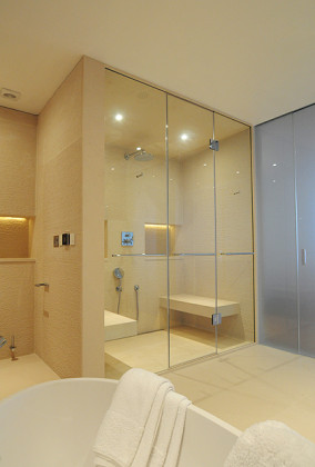 A luxury limestone bathroom in London with an SSI True frameless steam shower enclosure.