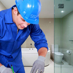 SSI Specialist glass installer in London wearing full PPE during installation of frameless bespoke shower enclosures